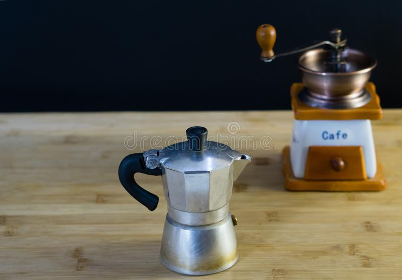 Old Italian Moka coffee maker. And manual coffee grinder in the background, wooden background royalty free stock photo