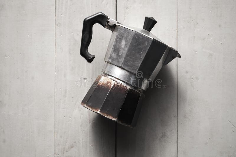 Old Italian moka pot lay on gray table. Old Italian moka pot lay on gray wooden table. It is a old stove-top coffee maker that brews coffee by passing boiling royalty free stock photos