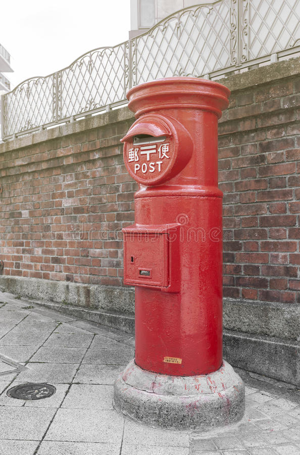 Old Japanese postbox stands beside a street in front of brick wall in a city of Japan with Japanese language translated as Post stock photo