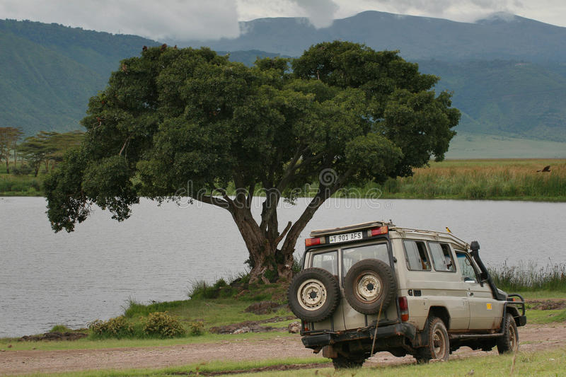 Old jeep for tourists, parked near forest lake, Ngorongoro crate stock image