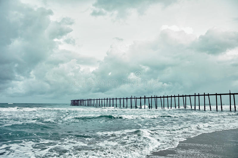 Old jetty over the stormy sea stock images