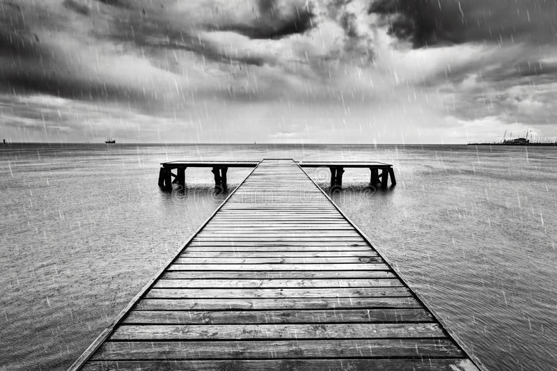 Old jetty, pier on the sea. Black and white, rain. Old wooden jetty, pier on the sea. Raining from dramatic sky with dark, heavy clouds. Black and white stock image