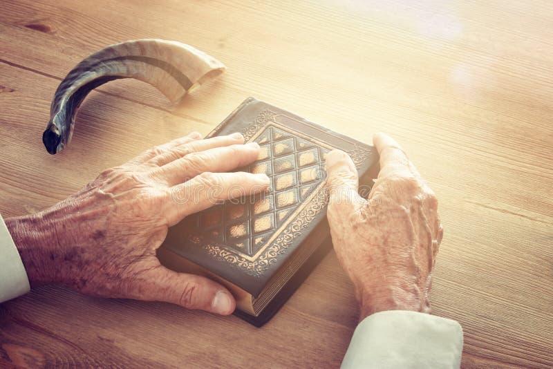 Old Jewish man hands holding a Prayer book, praying, next to shofar (horn). Jewish traditional symbols. Rosh hashanah (jewish New stock photo