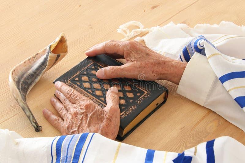 Old Jewish man hands holding a Prayer book, praying, next to tallit and shofar horn. Jewish traditional symbols. Rosh hashanah stock photography