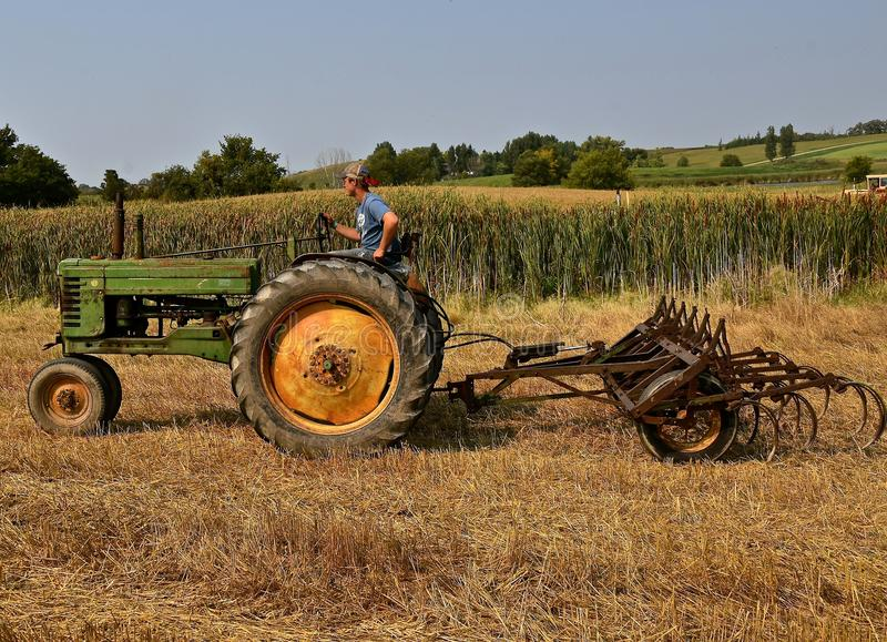 An old John Deere tractor and field cultivator. ROLLAG, MINNESOTA, Sept 2, 2017: An unidentified operator of an Old John Deere is heading for a field cultivator stock photos
