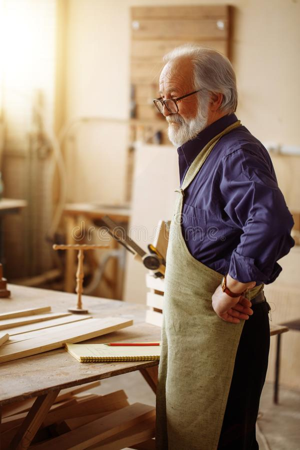 Old joiner with white hair, moustache nad beard resting in the workroom. Close up side view portrait of old joiner with white hair, moustache nad beard resting royalty free stock image