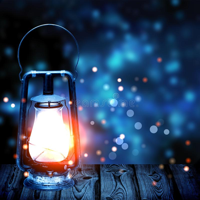 Old kerosene lamp shining in the dark blue blur in the background stock photography