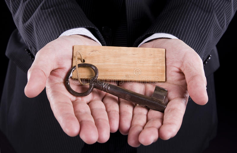 The old key. Businessman holding an old key (put your text on the wooden keychain stock photography