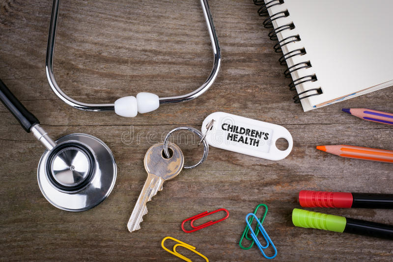 Old key With children's health Text. Wooden texture background w. Ith pencils, pens, stethoscope and notepad royalty free stock image