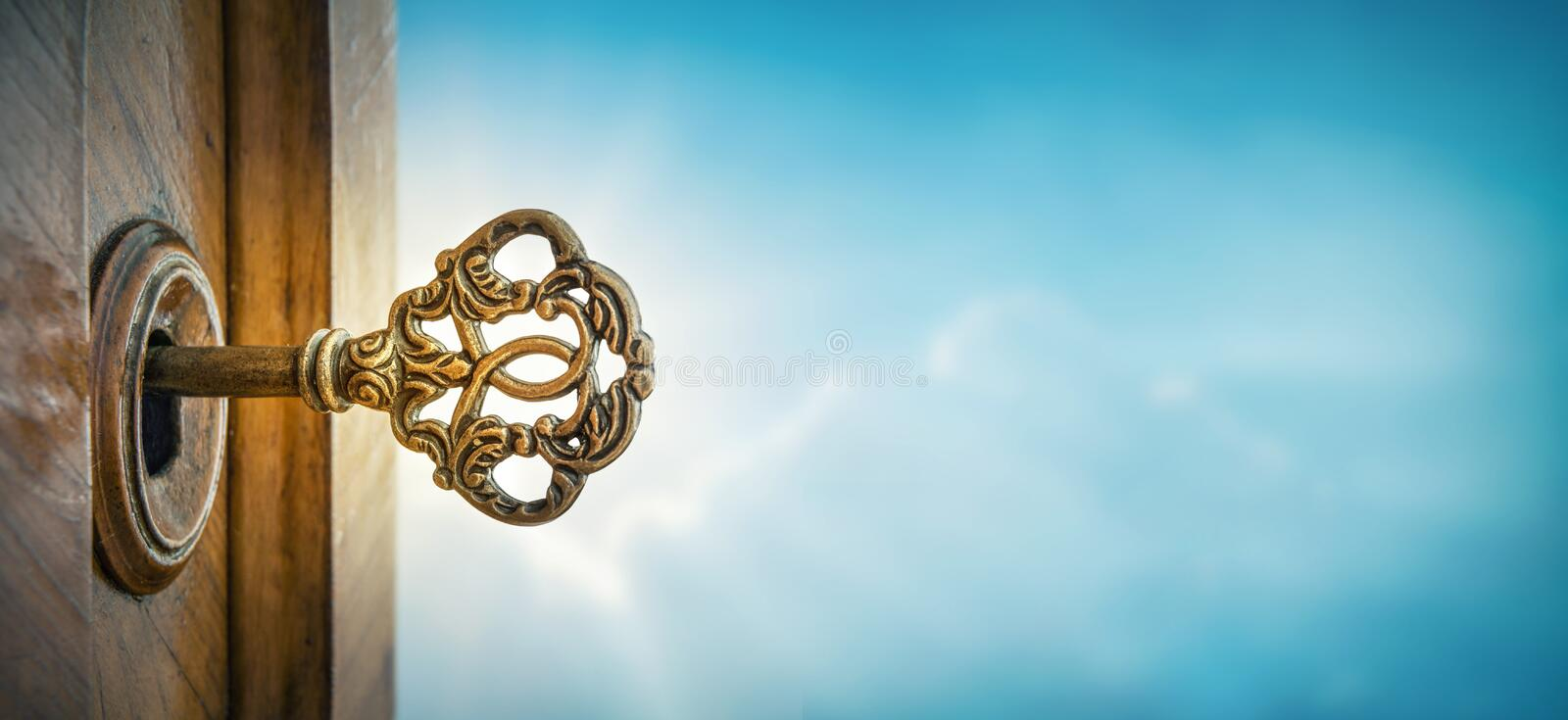 Old key in keyhole on sky background with sun ray . Concept, symbol and Idea for History, business, security background. Old key in keyhole on sky background stock photos