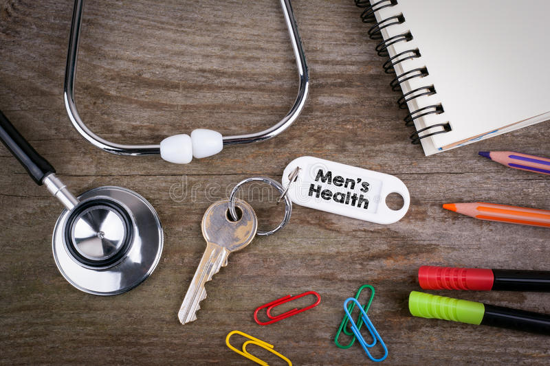 Old key With Men's Health Text. Wooden texture background with p. Encils, pens, stethoscope and notepad royalty free stock photos