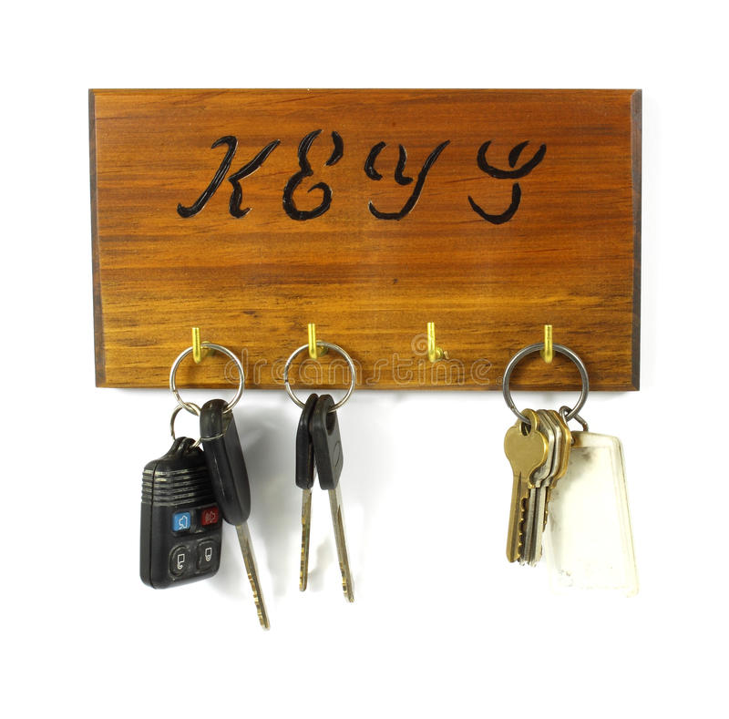 Old key rack with keys. A wood key rack holding three sets of keys on a white background royalty free stock photos