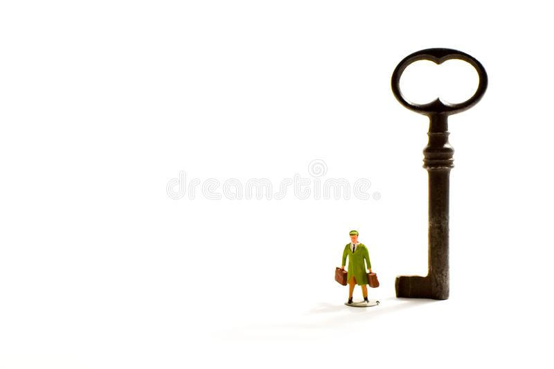 An old key on a white background with a miniature traveler stock photography