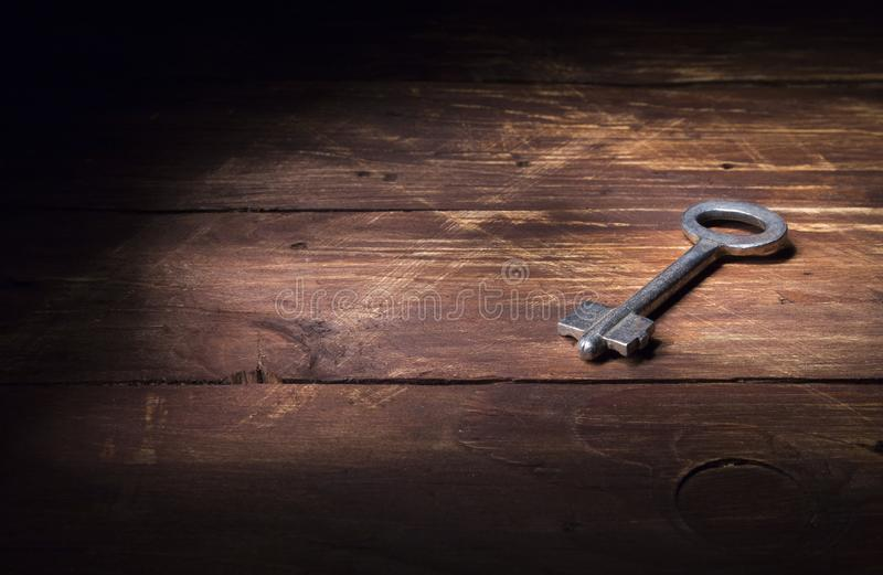 The old key of white metal lies on a wooden surface in a ray of light. royalty free stock image