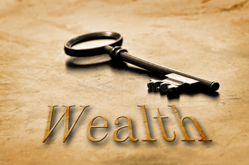 Key to Wealth and Riches. The key to wealth and riches laying on top of worn wood royalty free stock image