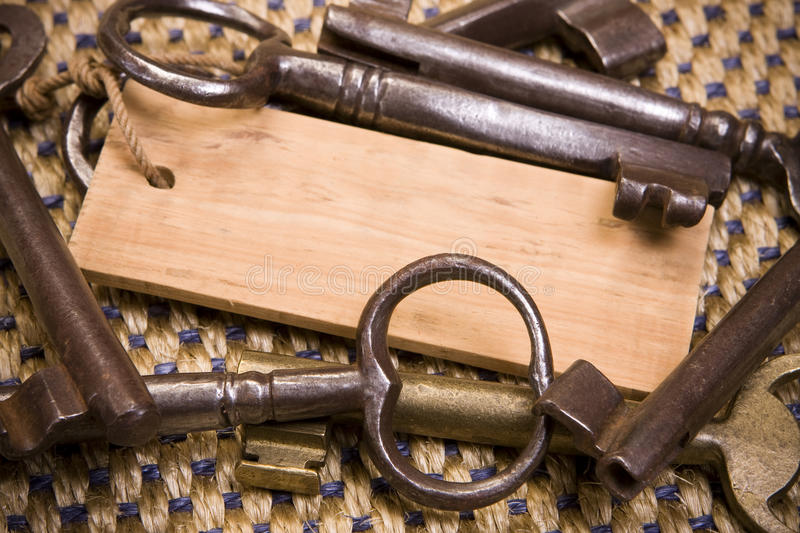 Old Keys. Many old rusty keys and a wooden keychain with space for text stock photo