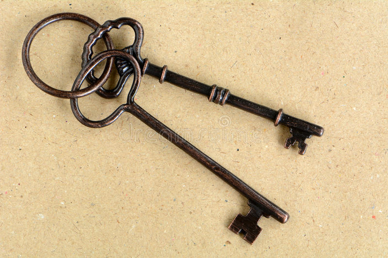 Old keys on antique paper. Old weathered keys on antique paper in horizontal format royalty free stock photography