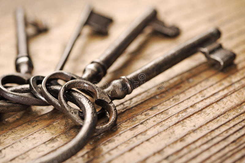 Old keys group. Old keys on a wooden table, close-up royalty free stock images