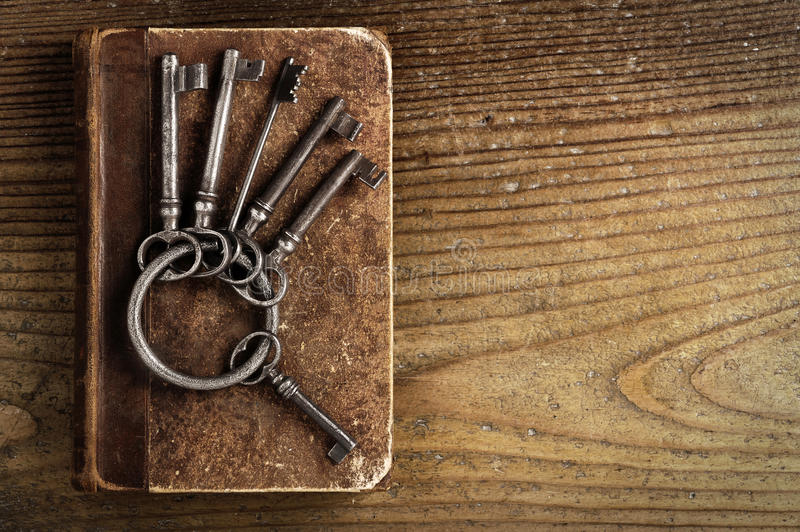 Old keys on a old book. Antique wood background stock images