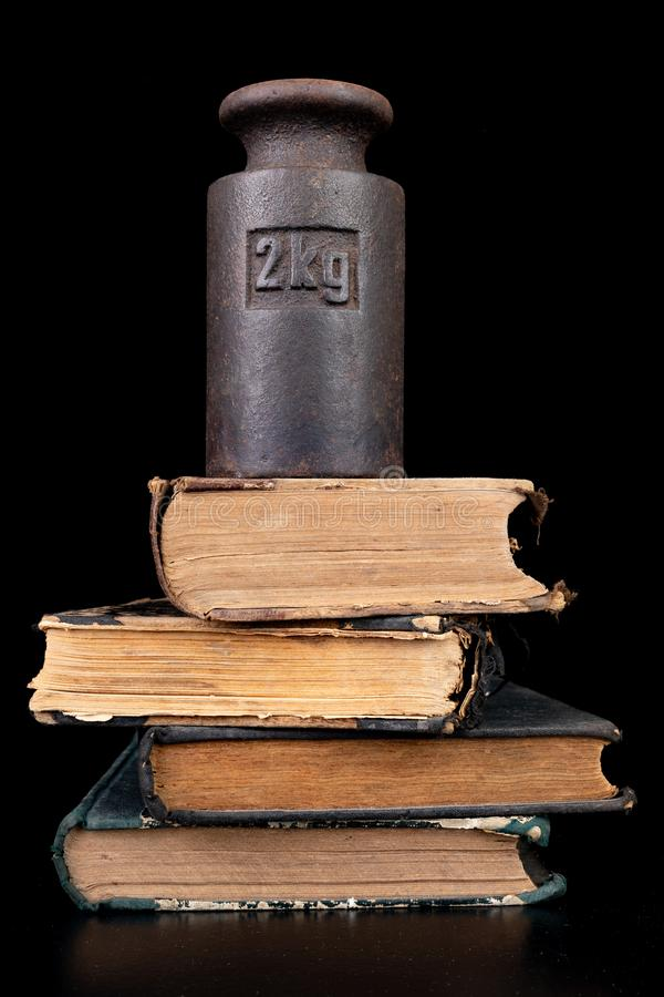 Old kilo weights on books. Old books and weighing machines stock photo