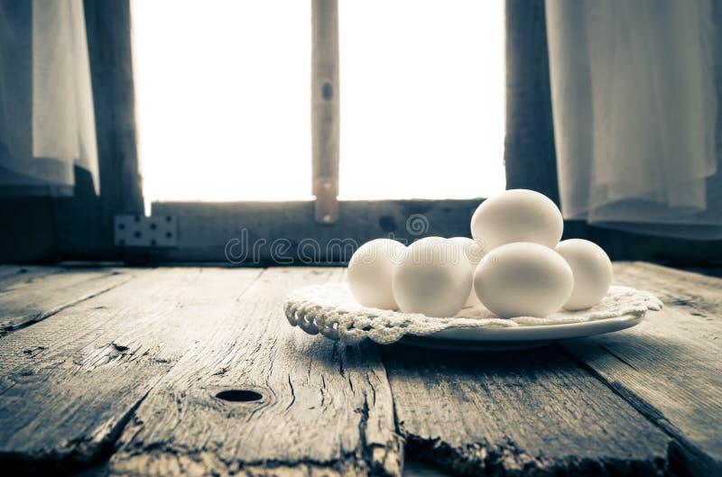 Old kitchen table rural hut morning egg. White egg on the kitchen table in a rural hut royalty free stock images