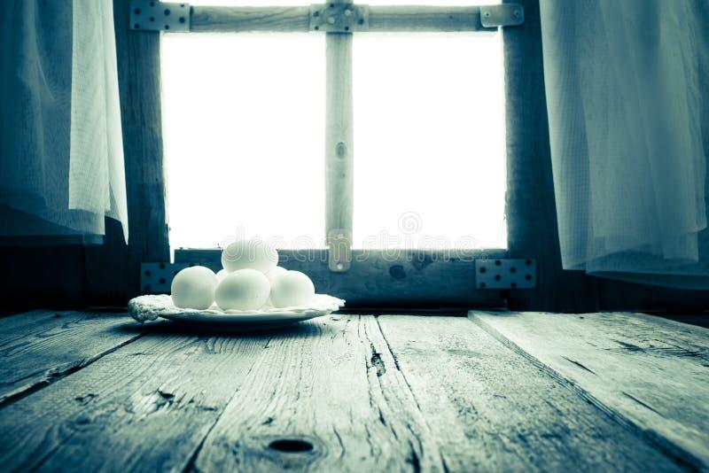 Old kitchen table rural hut morning egg. White egg on the kitchen table in a rural hut royalty free stock photo