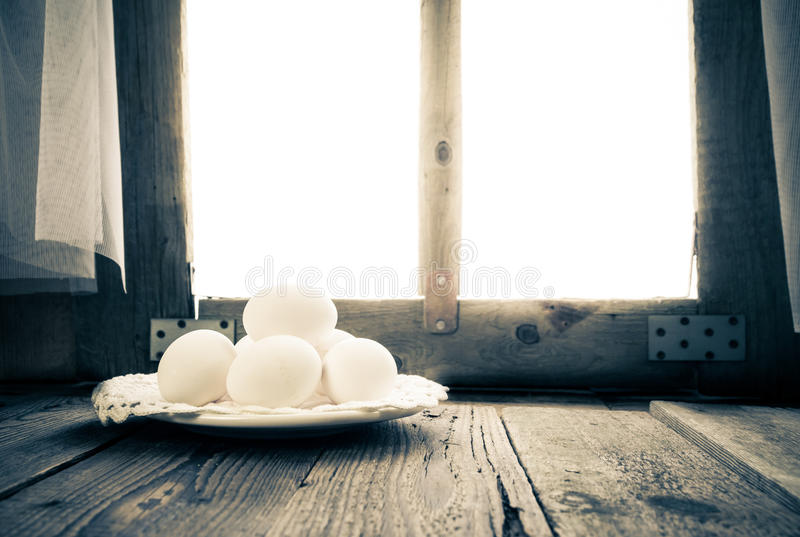 Old kitchen table rural hut morning egg. White egg on the kitchen table in a rural hut stock images