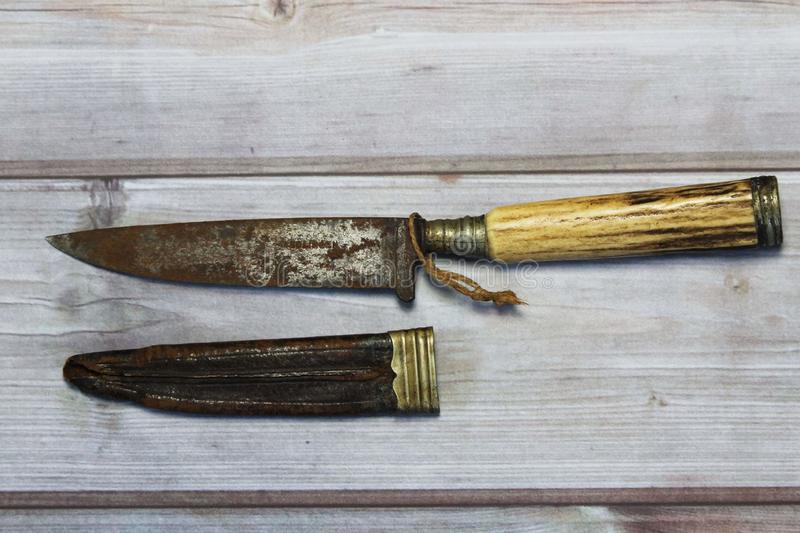 Old rusty knife. Old knife from a long time ago with leather knife holder stock photo