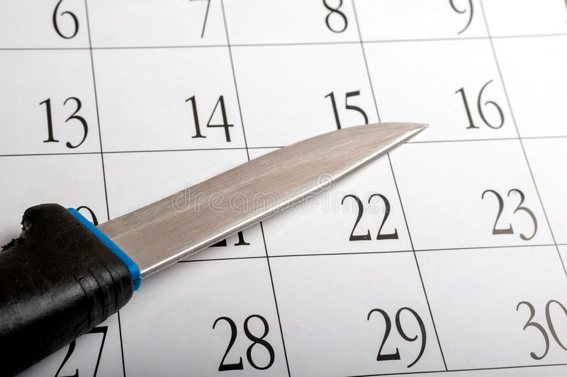 An old knife with a scratched blade on a calendar sheet with dates on it. Planning a homicide by a maniac stock photos