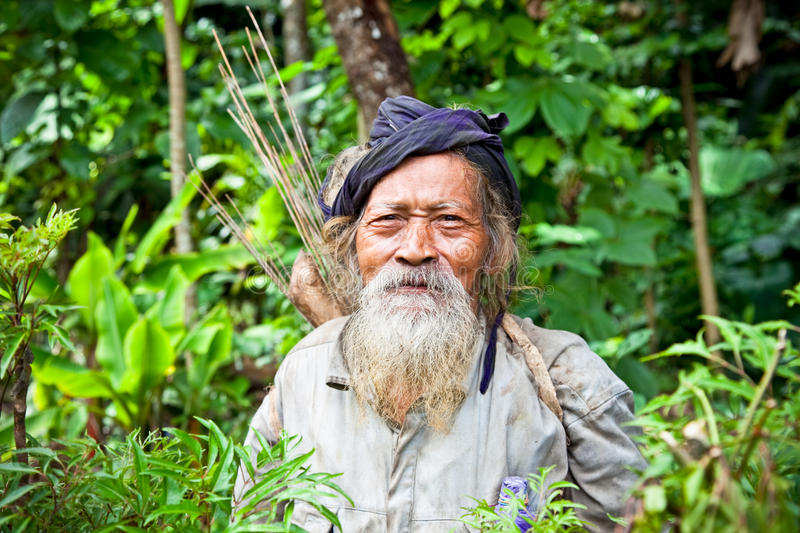 Old Kolufo man with bow and arrows in Blitar, Java, Indonesia. Old Kolufo man with bow and arrows on the natural green forest background in small village near royalty free stock photos