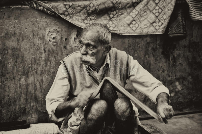 Old labourer in the Streets of New delhi. Old Man makes his living by doing shoe polish in the streets of New Delhi, India royalty free stock photo