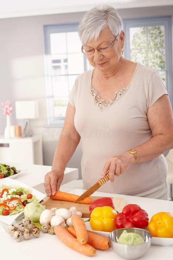 Old lady cooking healthy. Old lady preparing healthy food from fresh vegetables in kitchen, slicing carrots stock photography
