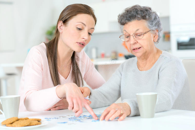 Old lady doing jigsaw puzzle. Old lady doing a jigsaw puzzle stock image