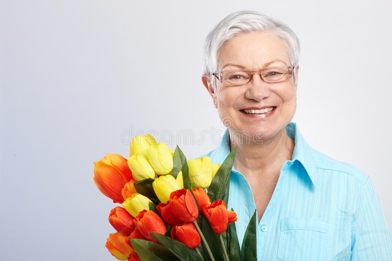 Old lady with flowers smiling. Old lady smiling, holding bouquet of flowers in hand stock photos