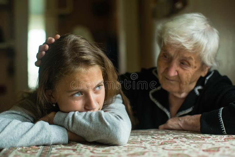 Old lady grandma comforting a crying little girl granddaughter. Helping. Old lady grandma comforting a crying little girl granddaughter stock images