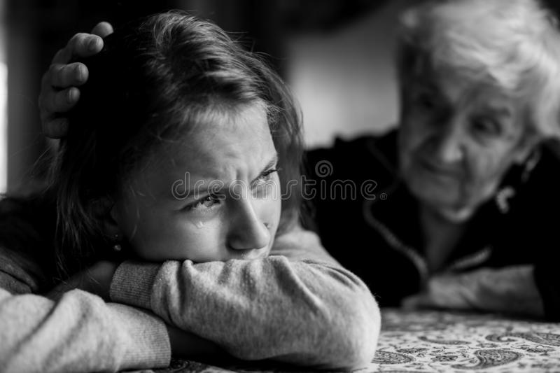 Old lady grandma comforting a crying little girl granddaughter. Black and white photo royalty free stock photos