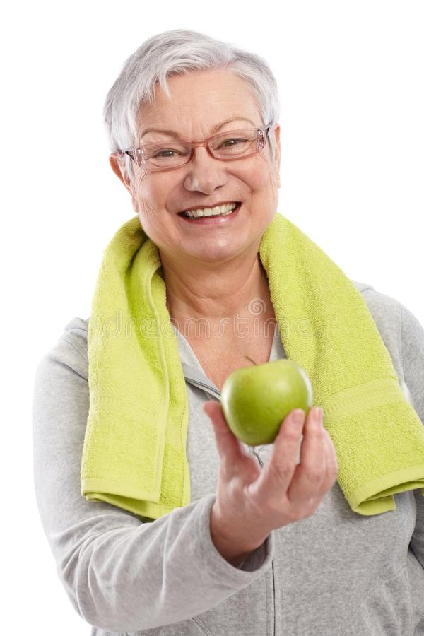 Old lady with green apple smiling. Old lady after workout holding green apple, smiling royalty free stock photos