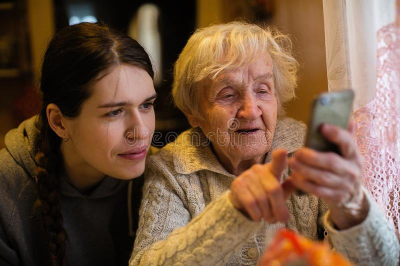 An old lady looks at a smartphone, with his adult granddaughter. Help. Источник: https://klaviatura.online.ua/en-ru/ royalty free stock photo