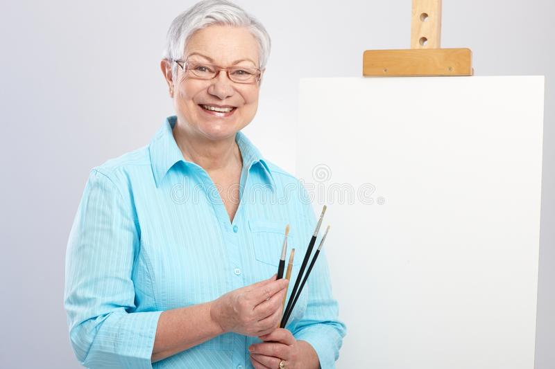 Old lady with paintbrush and canvas. Happy old lady as hobby painter with canvas and paintbrush stock photography