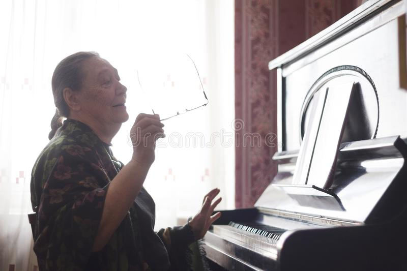 The old lady sitting in front of a piano and singing a song looking into a notebook royalty free stock photos