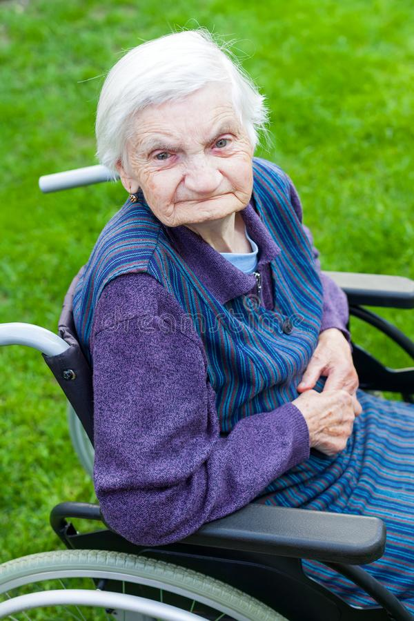 Old lady sitting in wheelchair royalty free stock photo