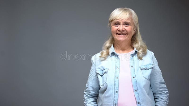 Old lady smiling into camera, looks healthy and trendy in casual denim clothes stock photography