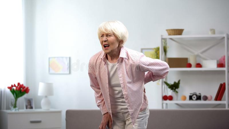Old lady standing up from sofa suddenly feeling sharp lower back pain, spasm stock images