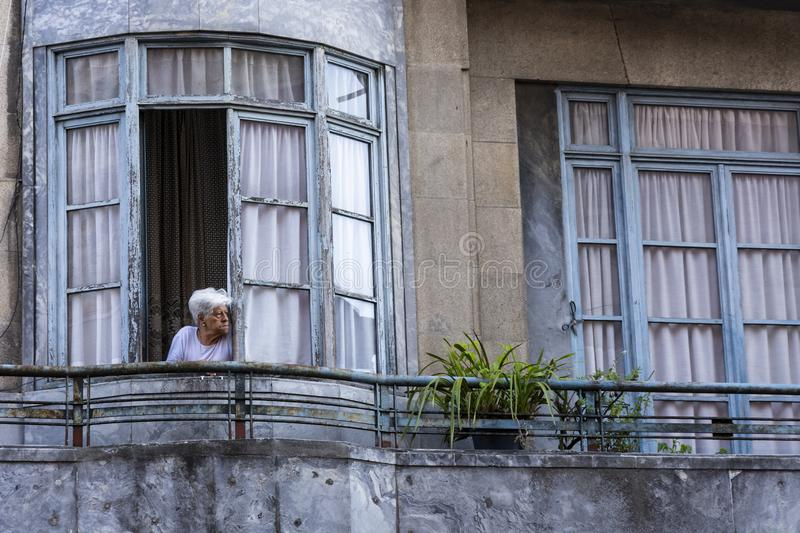 Old lady standing at the window, looking outside stock photo