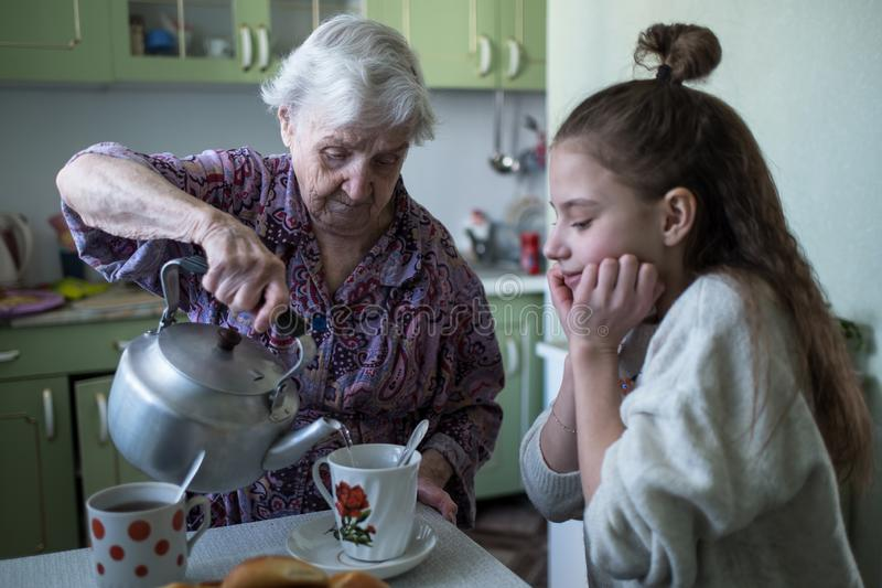 An old lady treats a little girl Breakfast, sitting at the table in his house. Grandmother and his lovely granddaughter royalty free stock photo