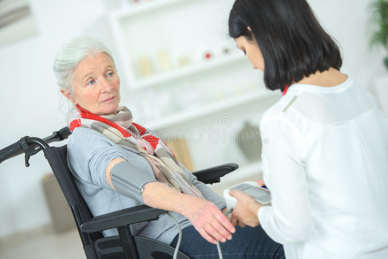 Old lady in wheelchair having blood pressure taken royalty free stock images