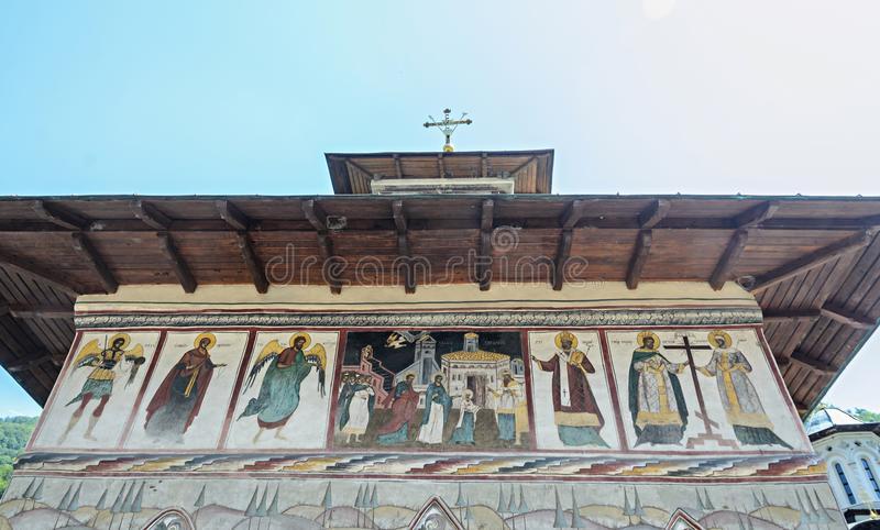 The old Lainici Monastery on a summer`s day, detail of the exterior painted wall stock photography