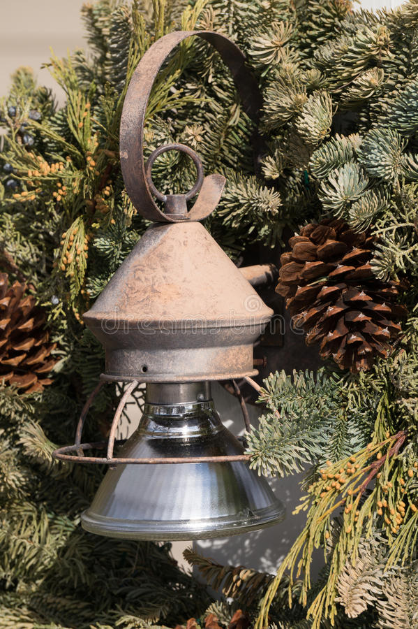Old Lamp. Evergreen wreath with old rusty lamp and pine cones royalty free stock photography