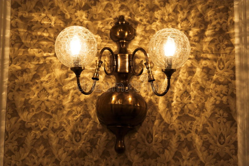 Old lamp and wallpaper. Old lamp on a wall with retro vintage wallpaper stock photography