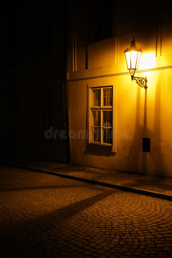 Old lantern illuminating a dark alleyway medieval street at night in Prague, Czech Republic. Low key photo. With brown yellow tones from the lanterns as single stock photography